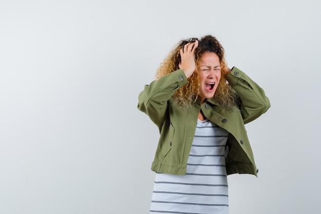 Donna meravigliosa che tiene le mani sulla testa e chiude gli occhi in giacca verde, camicia e sembra furiosa. vista frontale.