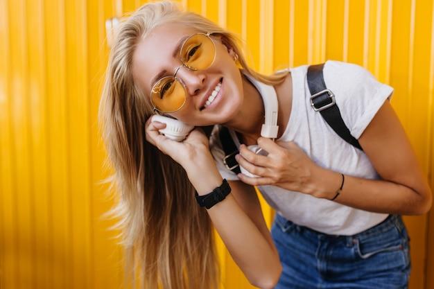 ポジティブな感情を表現する白いtシャツとジーンズの素晴らしい女性。黄色の背景にヘッドフォンで音楽を聴いている洗練された女性。