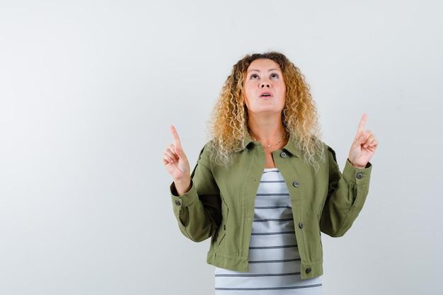 Donna meravigliosa che indica e che osserva in su in giacca verde, camicia e che sembra curiosa, vista frontale.