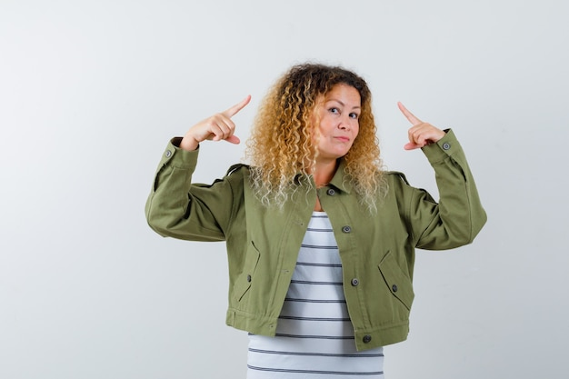 Wonderful woman pointing up in green jacket, shirt and looking confident . front view.