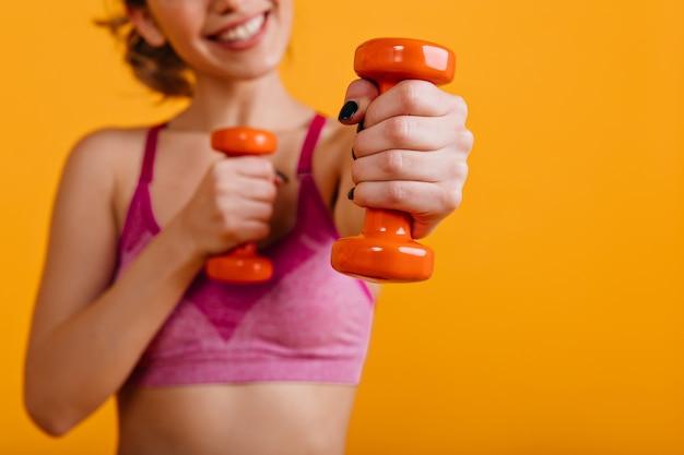 Wonderful woman using dumbbells in gym