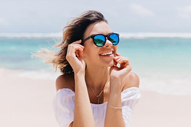 Wonderful woman in white attire and sparkle glasses posing with happy face expression in hot summer day. pleasant caucasian woman standing near ocean on sky