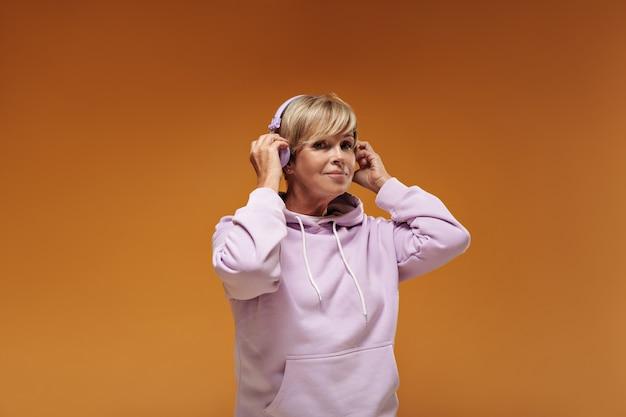 Splendida donna con acconciatura bionda e cuffie rosa in felpa con cappuccio elegante che esamina la macchina fotografica su sfondo arancione isolato.