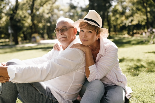 Wonderful woman with blonde hairstyle in trendy hat and pink shirt sitting on grass with man with mustache and white clothes in park.