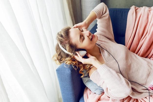 巻き毛の短い髪の素敵な女性がお気に入りの音楽を聴き、目を閉じて喜んで横になっています。かわいいピンクの部屋着。