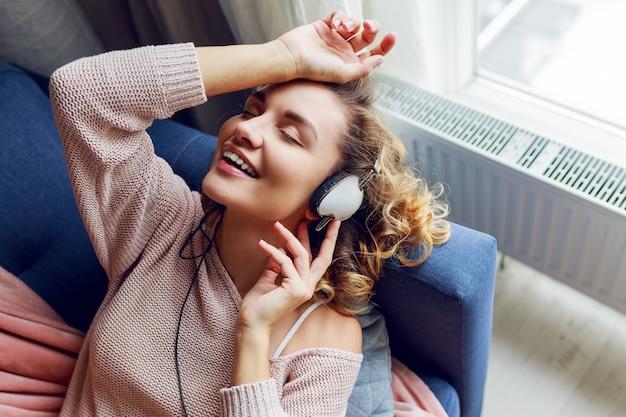 Meravigliosa donna con i capelli corti ricci ascolta la musica preferita e sdraiata con gli occhi chiusi con piacere. indossare abbigliamento da casa rosa carino.