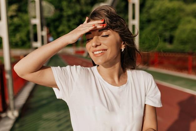 Замечательная женщина с длинными каштановыми волосами, закрывающими лицо от солнца и улыбающейся во время прогулки в солнечный день