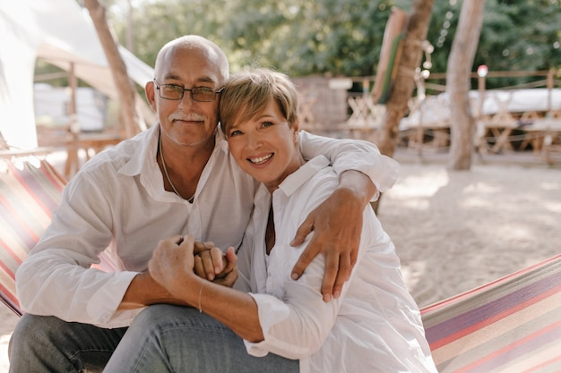 Wonderful woman with short blonde hairstyle in modern blouse smiling, sitting on hammock and hugging with her husband in eyeglasses on beach.