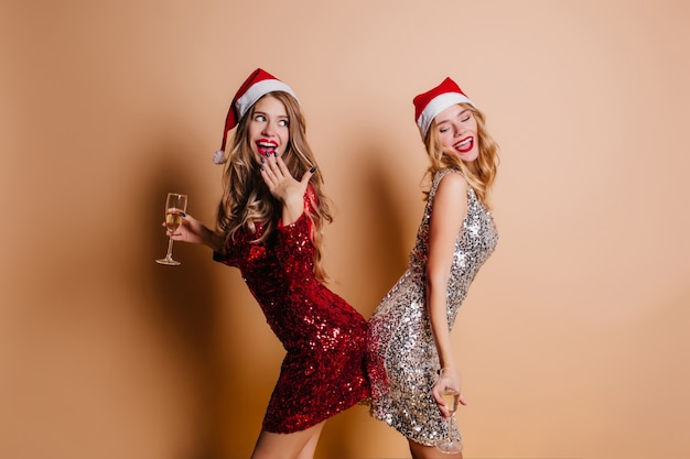 Wonderful women with curly hairstyle fooling around during new year photoshoot in room with light interior