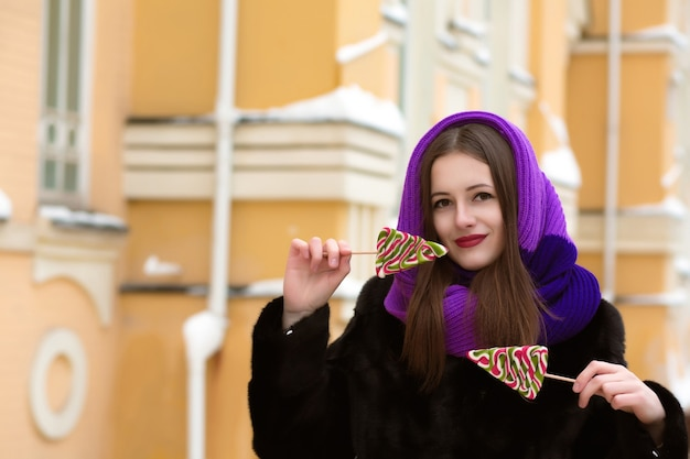 Wonderful young  brunette woman in purple scarf holding colorful christmas candies