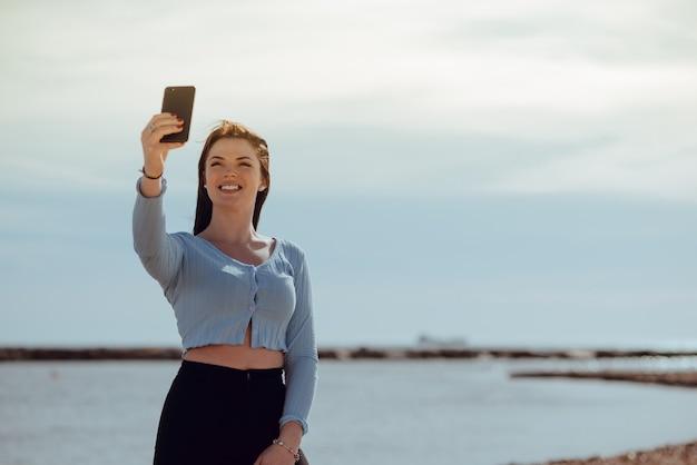 屋外の素敵な若い陽気で幸せな旅行者は、晴れた日に携帯電話で自画像を作成します