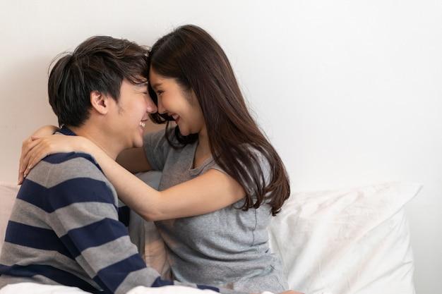 素晴らしい若いカップルは抱擁し、一緒に人生を楽しんで、朝はベッドで抱いて優しいカップルの笑顔