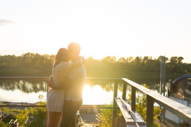 素敵な若いカップルが抱きしめ、自然の中での自然なアウトドアレジャー活動のライフスタイルと逆光の夕日と一緒に人生を楽しんでください。