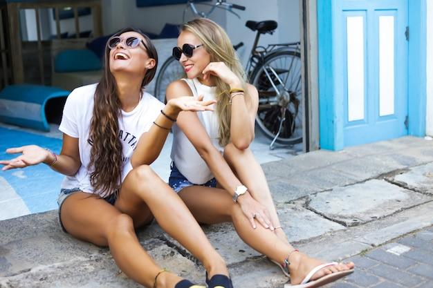 Замечательные молодые девушки сидят на улице у входа и смеются. блондинка и брюнетка дружат на отдыхе. летняя жаркая погода. носить белые футболки и джинсовые шорты. солнцезащитные очки на лице