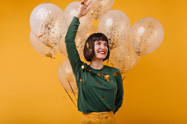彼女の誕生日に感情的にポーズをとる素晴らしい若い女性。パーティーを楽しんでいる黒髪の女の子を笑っています。
