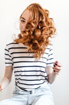 놀라운 곱슬 헤어 스타일 포즈와 멋진 젊은 아가씨. 붉은 머리를 가진 매력적인 백인 여자의 실내 샷.
