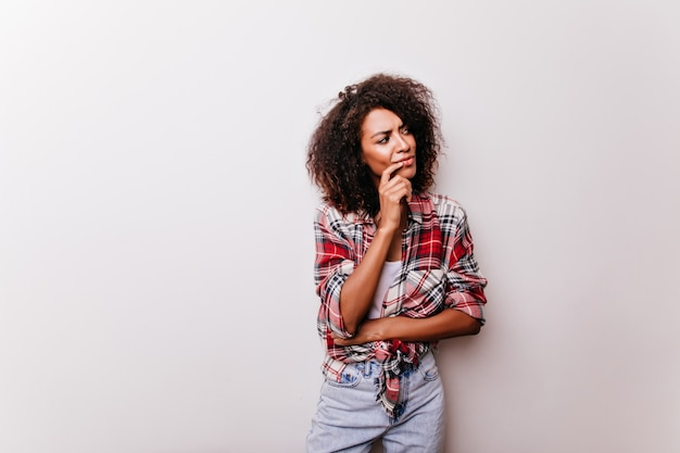 Замечательная барышня с каштановыми короткими волосами о чем-то думает. потрясающая стильная африканская девушка.