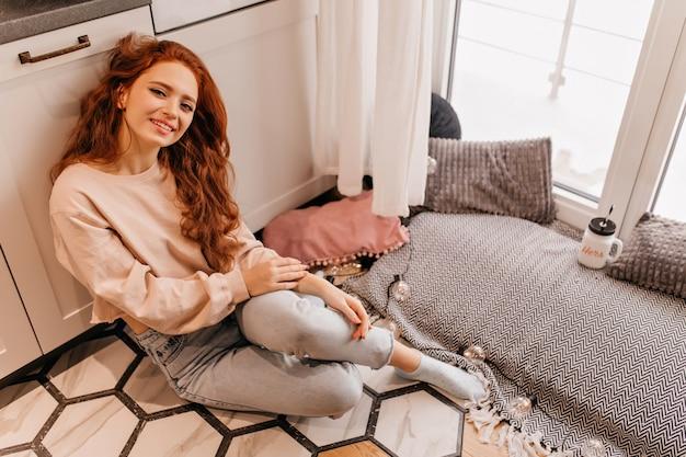 Замечательная молодая дама с рыжими волосами улыбается. крытое фото радостной кавказской девушки, сидящей дома.