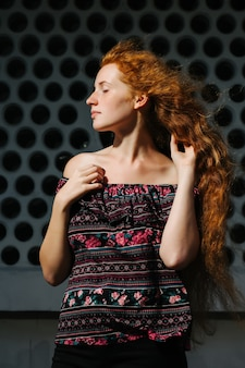 そばかすのある素晴らしい若い赤い髪のモデル。裸の肩でポーズをとって目を閉じた女性