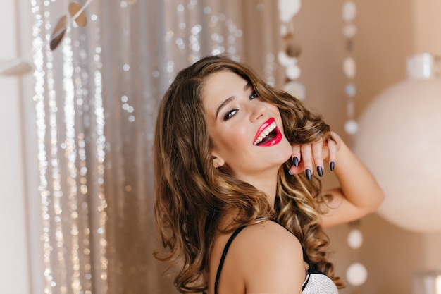 Wonderful young white lady with shiny dark hair posing with pleasure at christmas party. lovable caucasian woman expressing happiness during photoshoot at event.