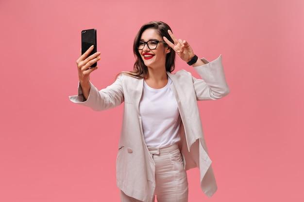 Замечательная молодая женщина в стильных очках и бежевой куртке делает селфи и показывает знак мира на розовом изолированном фоне.
