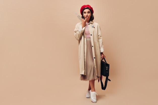 Замечательная молодая женщина в стильном красном берете и бежевом плаще выглядит удивленной и держит билеты на изолированном фоне.