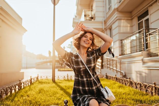 Замечательная молодая женщина позирует в солнечный осенний день. смеющаяся модная белая дама, расслабляющаяся в сентябре утром.