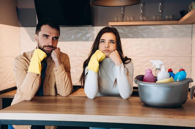 自宅のモダンなキッチンで家の掃除をしている不思議なカップル。洗剤と妻と一緒に洗っている若い男性ときれいな女性の写真。