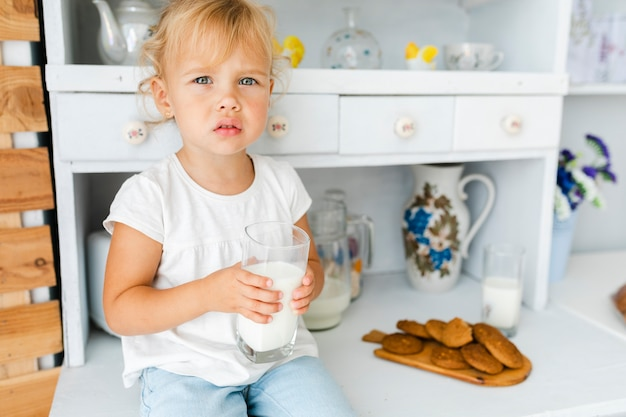 Wondering girl holding a glass of milk