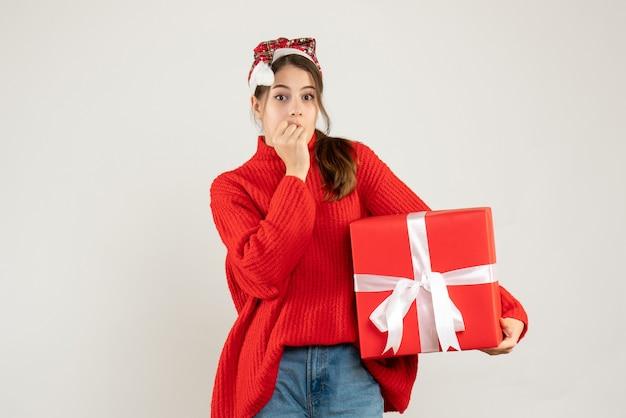 白の上に立っている彼女の口に手を置いてプレゼントを持っているサンタの帽子を持つ不思議な女の子