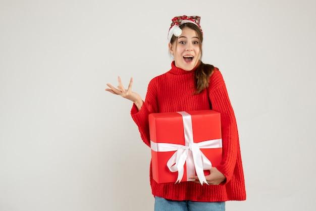 白の上に立っているプレゼントを持っているサンタの帽子を持つ不思議な女の子