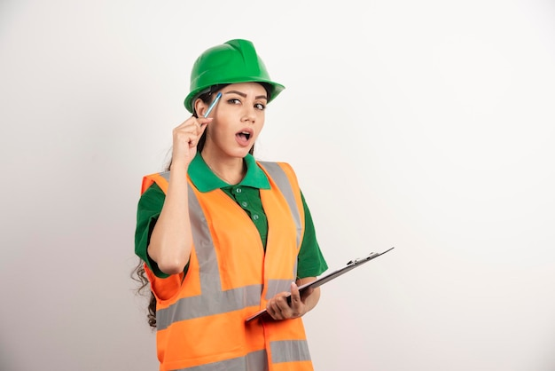 Wondering woman builder with clipboard on white background. high quality photo