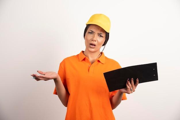 Интересно женщина-курьер с карандашом, держащим доску сзажимом для бумаги на белой стене.