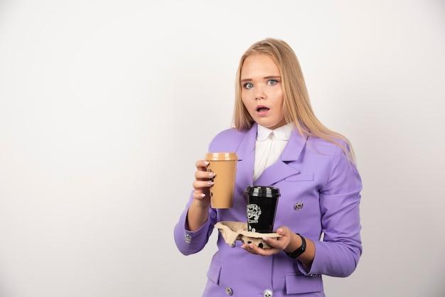 Chiedendosi donna che tiene due tazze di caffè su priorità bassa bianca. foto di alta qualità