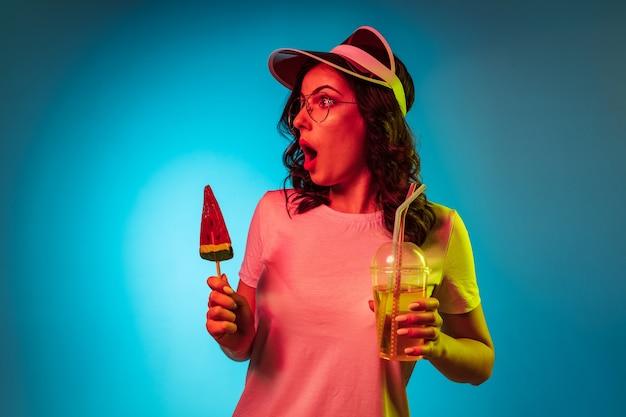 トレンディな青いネオンスタジオでお菓子と飲み物を保持している帽子の若い女性を不思議に思う