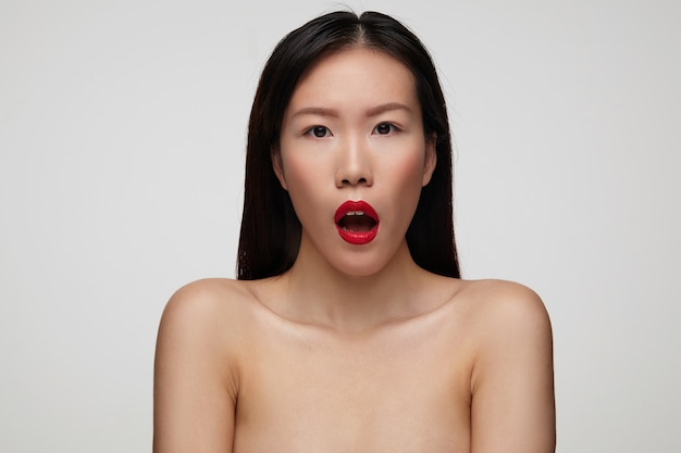 놀랍게도 그녀의 입을 벌리고 흰 벽에 고립 된 붉은 입술을 가진 wonderstruck 젊은 매력적인 검은 머리 아가씨