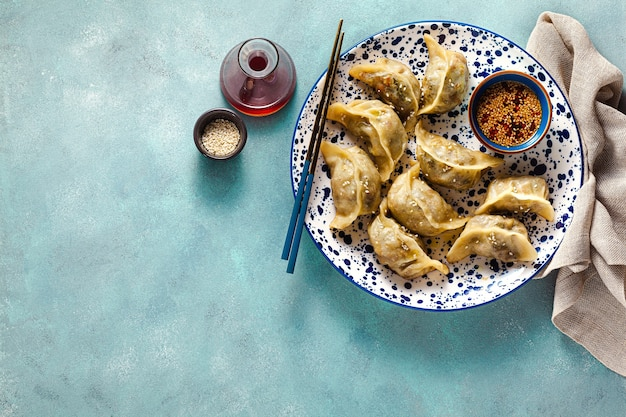 Wonton dumplings with spicy sesame sauce on the table.