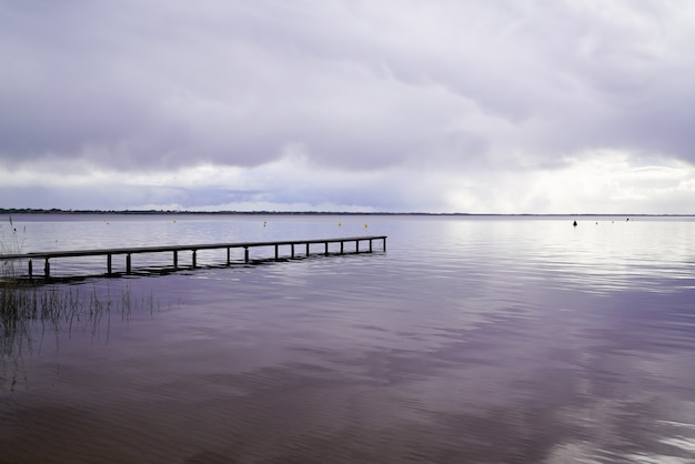 Wood access empty pontoon sunrise blue water winter on lake hourtin in gironde france