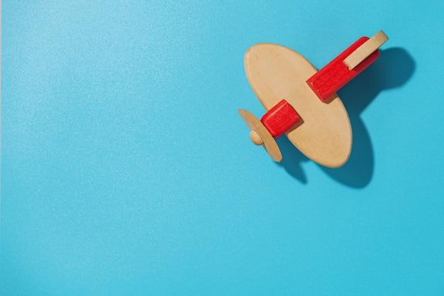 Деревянный самолет на синем фоне, вид сверху
