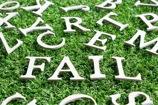 Wood alphabet in wording fail  on artificial green grass background