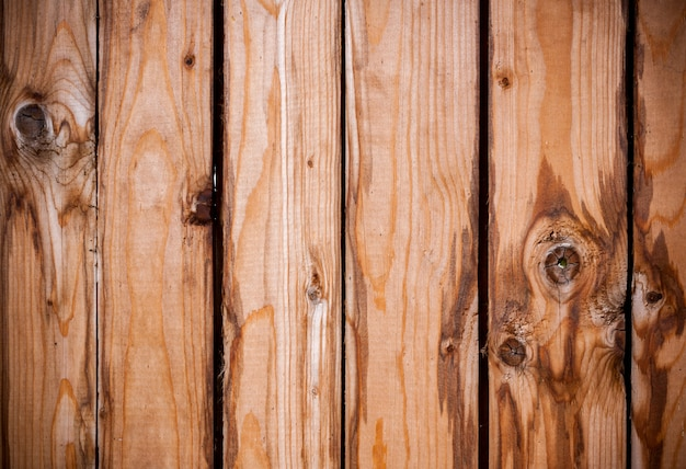 Wood background of old brown vertical boards with knots and stains.