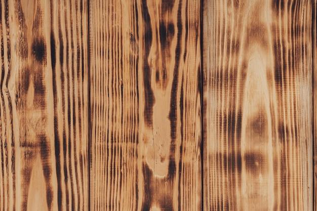 焦げた木の効果を持つ木の背景。焦げた板の質感