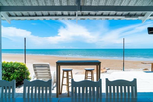 Wood bar and chair with ocean sea beach and blue sky