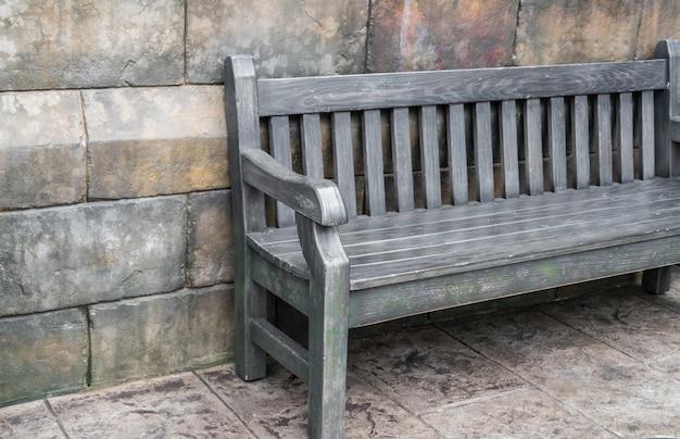 Деревянная скамья против бетонной стены.