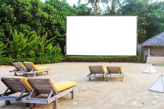 木の森の背景に白いスクリーンと砂浜の木ベンチ