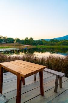 Деревянная скамейка с красивым озером в чиангмае с лесными горами и сумеречным небом в таиланде.