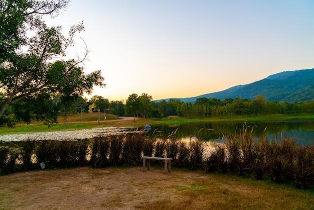 태국의 숲이 우거진 산과 황혼의 하늘이 있는 치앙마이의 아름다운 호수가 있는 나무 벤치.