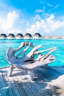 Деревянная скамейка с тропическим мальдивским курортом и островом для концепции отпуска
