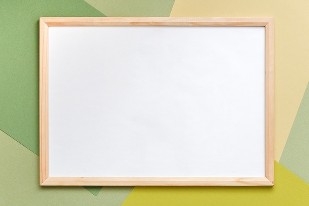 Wood blank frame on geometric green shades paper background. copy space, mockup for your design, text