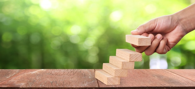 Деревянный блок в руке укладки в качестве ступеньки. рост бизнес-концепции
